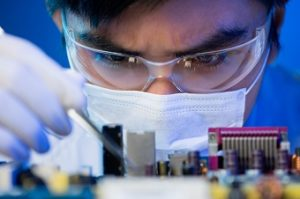 Close-up image of an engineer concentrated on electronic assembling on the foreground