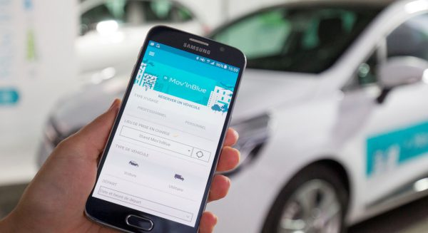 A woman using the Valeo Mov'In Blue App to reserve a vehicle using her smartphone